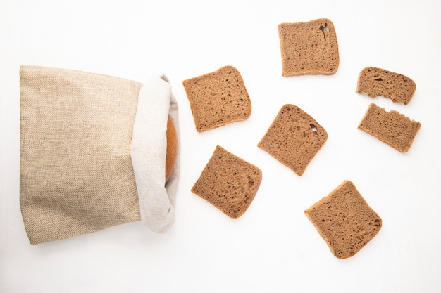 Top view of rye bread slices and sack with bread on white background with copy space Free Photo