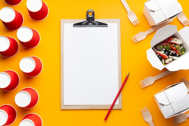 Top view salad with clipboard on yellow background Free Photo