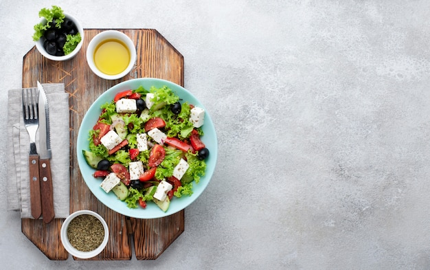 Top view salad with feta cheese on cutting board with copy-space Free Photo