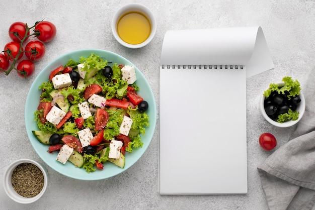 Vista dall'alto insalata con formaggio feta, pomodori e olive con blocco note vuoto Foto Gratuite