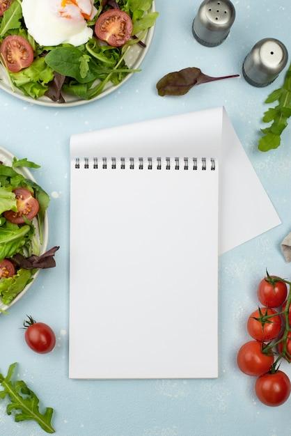 Салат вид сверху с жареным яйцом и помидорами с пустой записной книжкой Бесплатные Фотографии