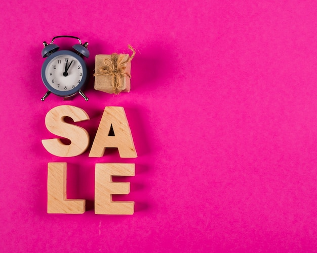 Top view of sale word and clock on pink background Free Photo