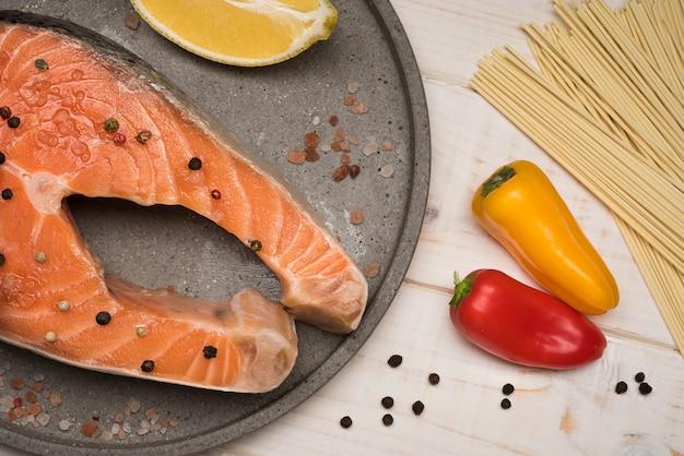 Вид сверху стейк из лосося на подносе с перцем Бесплатные Фотографии