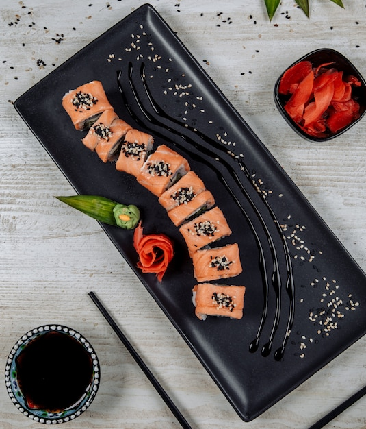 Top view of salmon sushi roll served with ginger, wasabi and soy sauce Free Photo
