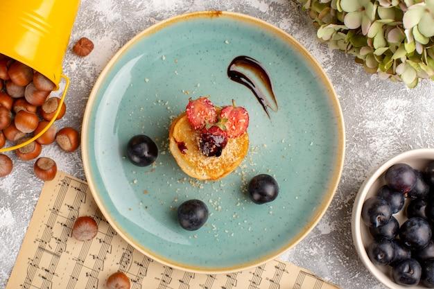 Vista dall'alto patatine salate progettate con fragole all'interno del piatto insieme a prugnoli sul tavolo bianco, patatine fritte snack frutta bacca Foto Gratuite