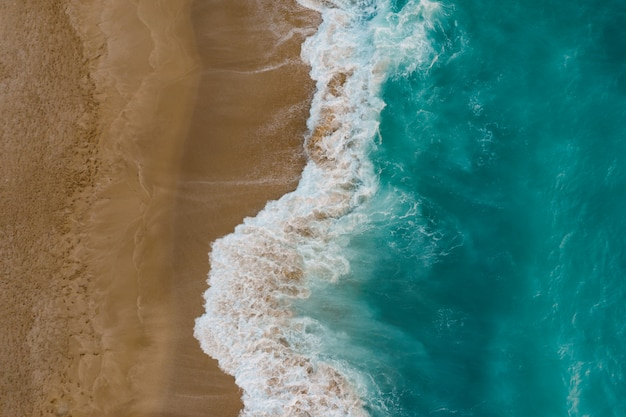 Vista dall'alto della sabbia che incontra l'acqua di mare Foto Gratuite