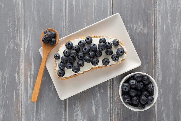 Vista dall'alto panino con crema di formaggio e mirtilli sulla piastra con cucchiaio Foto Gratuite