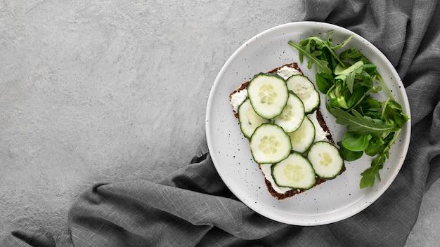 Vista dall'alto panino con cetrioli sulla piastra con carta da cucina Foto Gratuite