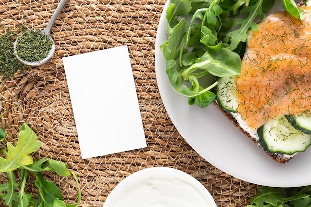 Vista dall'alto panino con cetrioli e salmone sul piatto con rettangolo vuoto Foto Gratuite