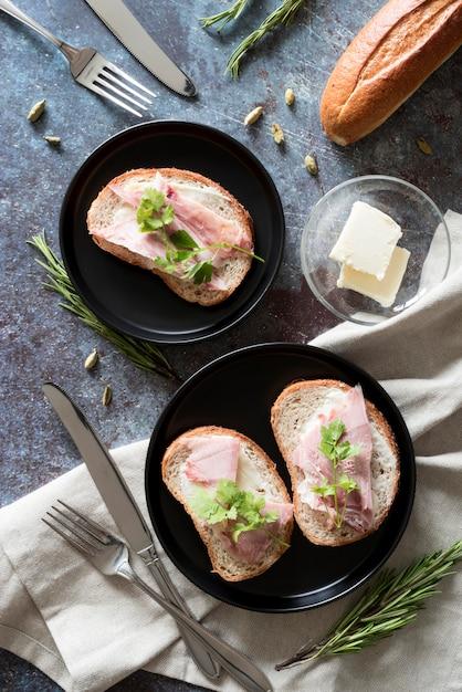 Vista dall'alto panini con burro e prosciutto sul piatto Foto Gratuite