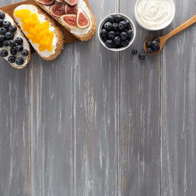 Vista dall'alto panini con crema di formaggio e frutta con copia-spazio Foto Gratuite