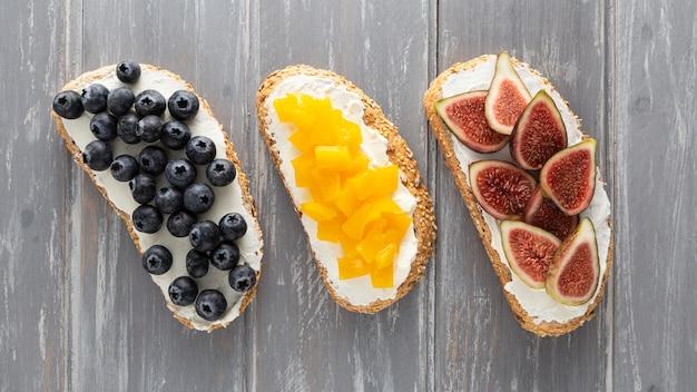 Vista dall'alto panini con crema di formaggio e frutta Foto Gratuite