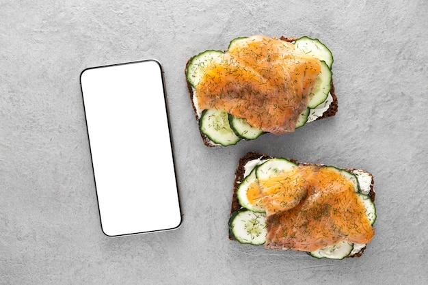 Vista dall'alto panini con cetrioli e salmone con telefono vuoto Foto Gratuite
