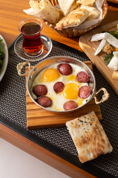 A top view sausage with eggs along with tea and bread loafs on the restaurant table food meal breakfast Free Photo