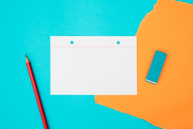 Top view of school supplies and card paper on turquoise background Free Photo