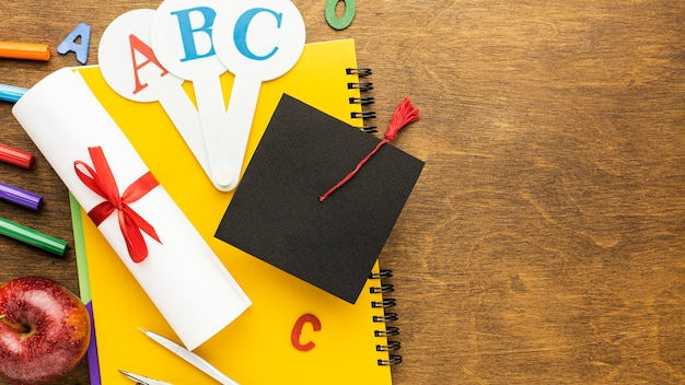 Top view of school supplies with academic cap and copy space Free Photo
