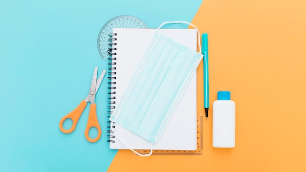 Top view of school supplies with notebook and medical mask Free Photo
