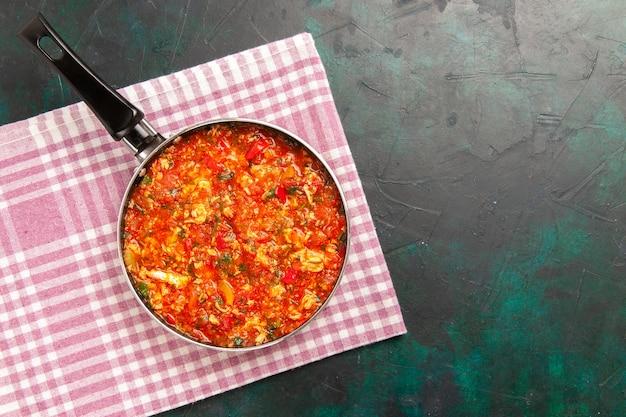 濃い緑色の背景の鍋の中にトマトと緑のスクランブルエッグの上面図 無料写真