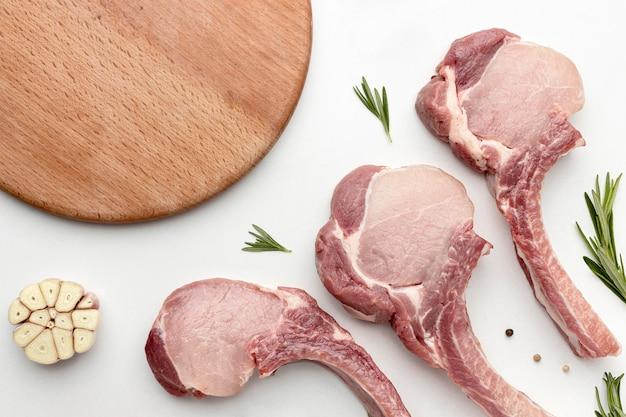 Вид сверху приправленное мясо для приготовления пищи с деревянной доской Premium Фотографии