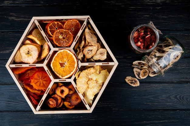 Top view of a set of dried fruits in a wooden box and dried banana and strawberry chips in glass jars on black background Free Photo