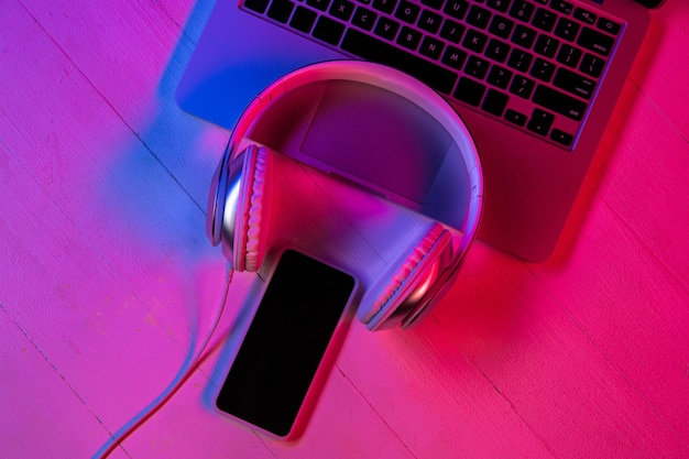 Top view of set of gadgets in purple neon light and pink background. laptop keyboard, headphones and smartphone with black screen. copyspace for your advertising. tech, modern, gadgets. Free Photo
