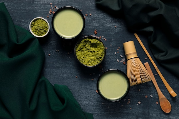 Top view set of green tea powder next to tradiotional utensils Free Photo