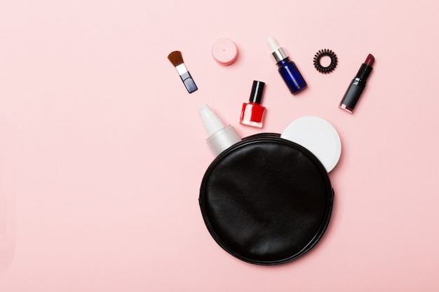 Top view of set of make up and skin care products spilling out of cosmetics bag Premium Photo