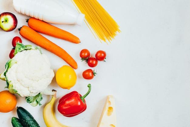 自由空間と白い背景の上の食品野菜果物と乳製品の上面図セット Premium写真