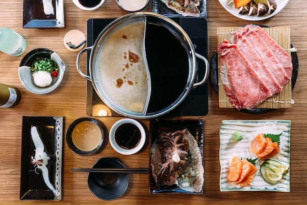 Top view of shabu set including rare slices wagyu a5 beef, shabu shoyu and clear base. Premium Photo