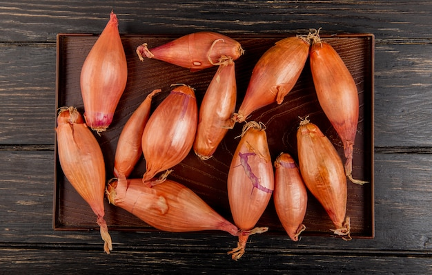 Top view of shallots in tray on wooden background Free Photo