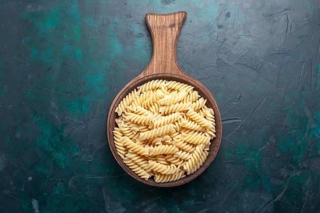 トップビューの形をしたイタリアンパスタダークブルーの机の上にある美味しそうな小さなパスタ 無料写真