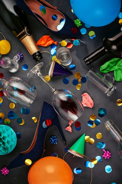 Top view shot of after a party celebration with empty bottles,wine glass, girl shoes and party accessories Premium Photo