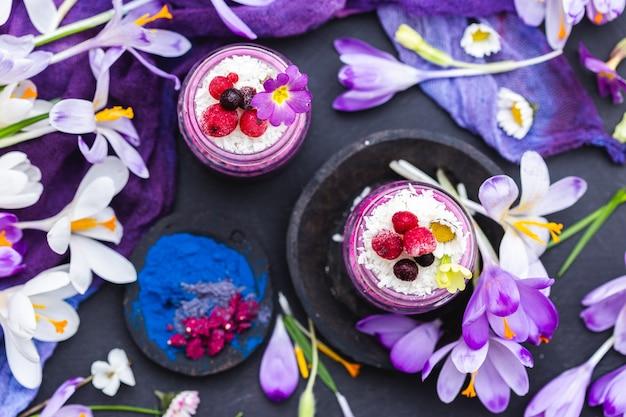 Vista dall'alto di un bellissimo display di frullati vegani viola adornati con fiori colorati Foto Gratuite