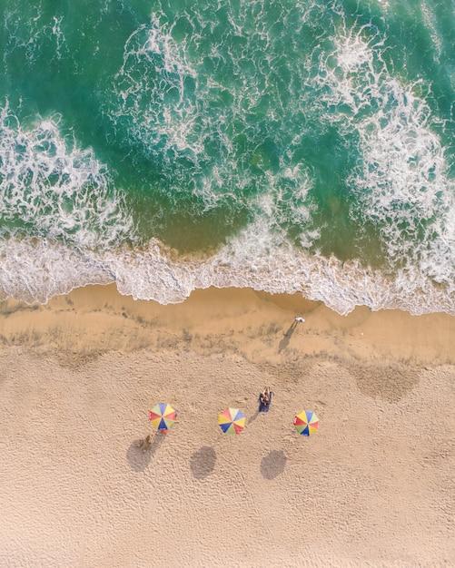 Вид сверху на пляжные зонтики и людей, лежащих на песке на пляже варкала Бесплатные Фотографии