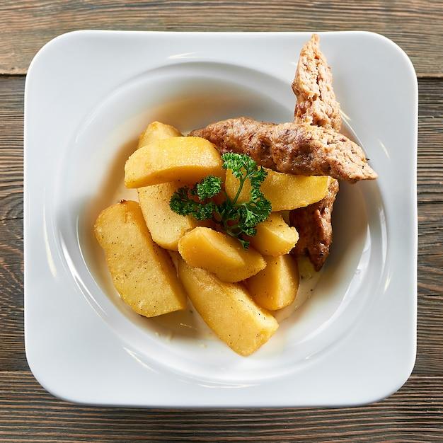 레스토랑 고기 음식 영양 지방 칼로리 식사 메뉴 주문 미식가 봉사 부분에서 제공되는 접시에 구운 감자와 닭고기 소시지의 상위 뷰 샷. 무료 사진