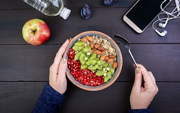 Top view showing hands eating healthy oatmeal with kiwi and almond on a wooden table. Premium Photo