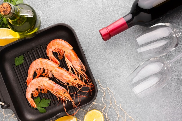 Top view shrimp in pan with wine bottle Free Photo