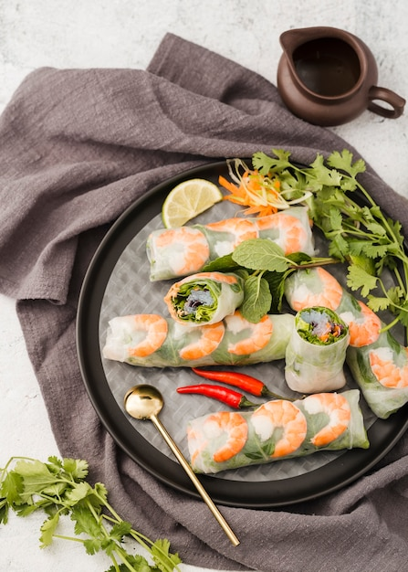 Top view of shrimp rolls on plate with sauce Free Photo