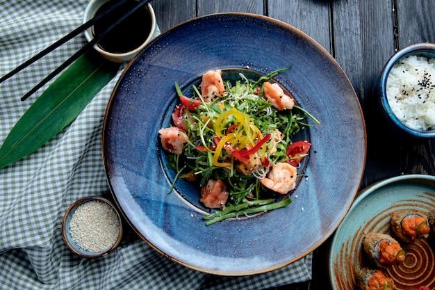Vista dall'alto di insalata di gamberi con peperoni e rucola su un piatto su legno Foto Gratuite