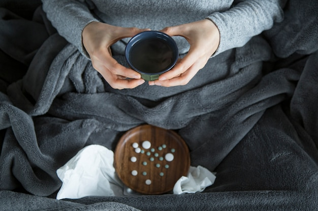 Top view of sick woman on sofa, holding green cup in hands Free Photo