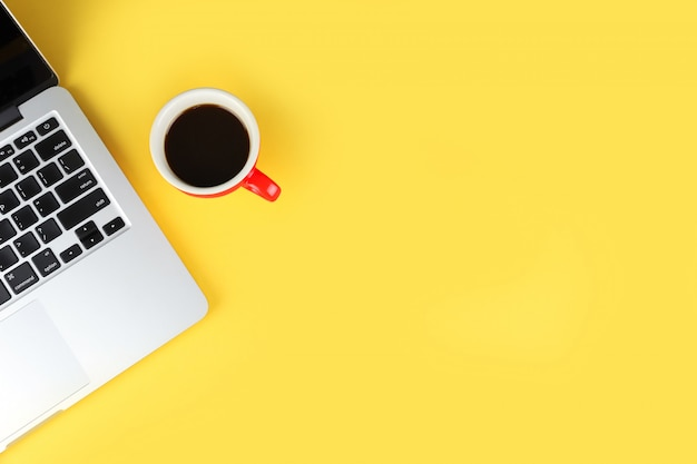 Top view of simple business office table with workspace laptop computer and red coffee cup Premium Photo