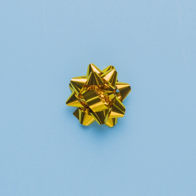 Top view of a single gift bow on plain blue surface Free Photo