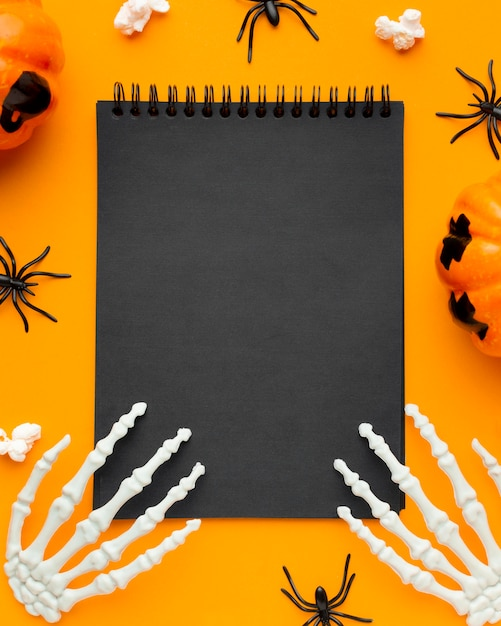 Top view skeleton hands on notepad for halloween Free Photo
