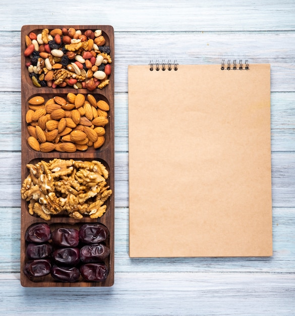 Top view of sketchbook and nuts mix with walnuts almond and sweet dried date fruits on wooden Free Photo