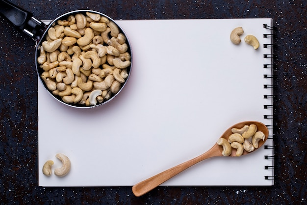 Top view of sketchbook and a pan with cashew and a wooden spoon with nuts on black background Free Photo