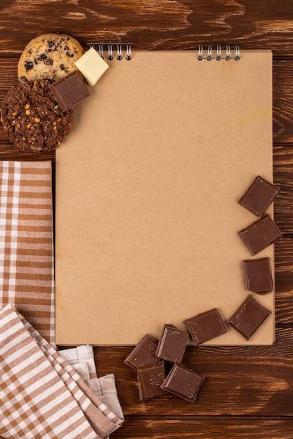 Vista superiore dello sketchbook con pezzi di cioccolato fondente e biscotti di farina d'avena su fondo di legno Foto Gratuite