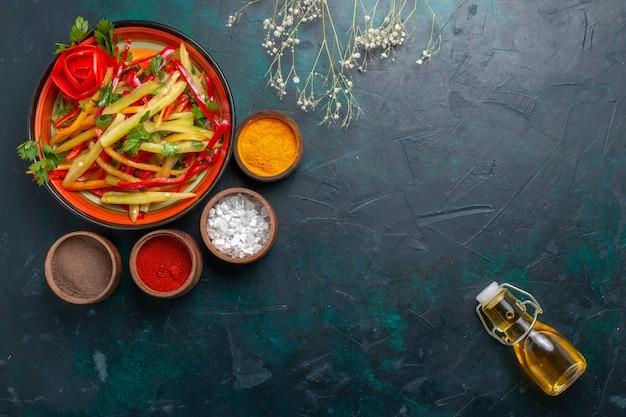 Vista dall'alto di peperoni affettati insalata sana con olio d'oliva e condimenti su sfondo blu scuro Foto Gratuite