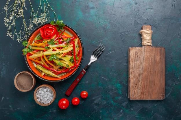 暗い背景に調味料とメモ帳でスライスしたピーマンのおいしい健康的なサラダの上面図 無料写真