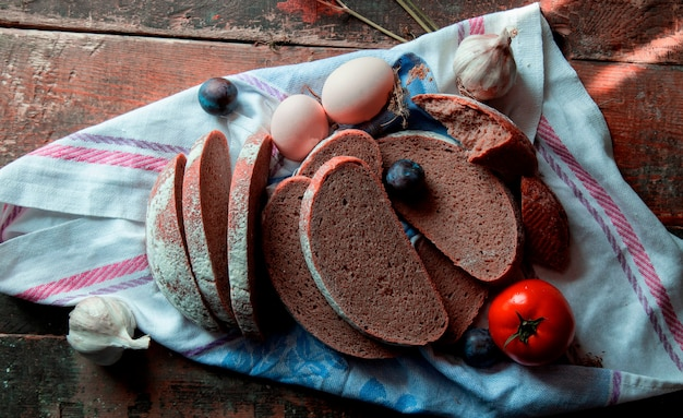 Top view sliced black bread, eggs, plums, garlic gloves and tomatoes on a white tablecloth . Free Photo
