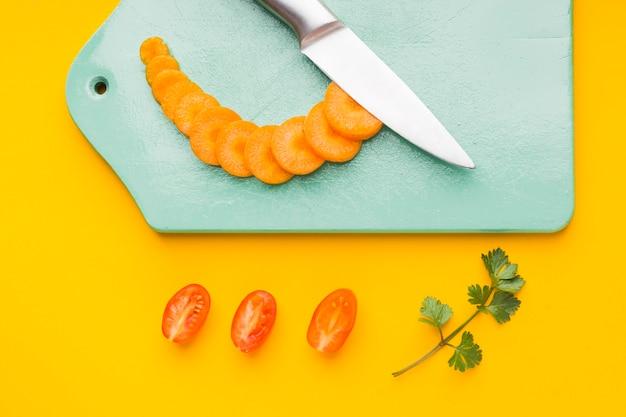 Вид сверху нарезанная морковь на разделочной доске с помидорами Бесплатные Фотографии